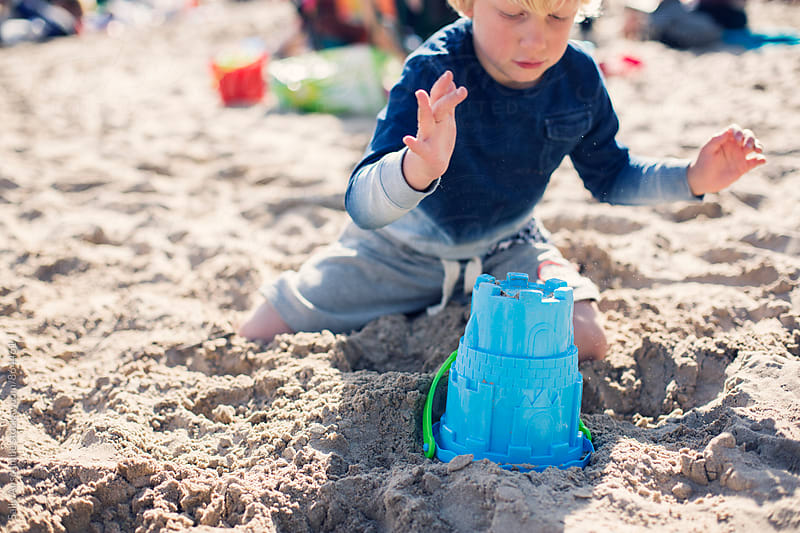 Child building a sandcastle on the beach by sally anscombe for Stocksy United