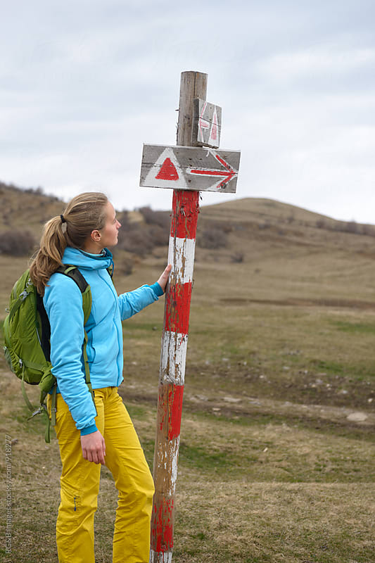Hiker standing next to trekking sign by RG&B Images for Stocksy United