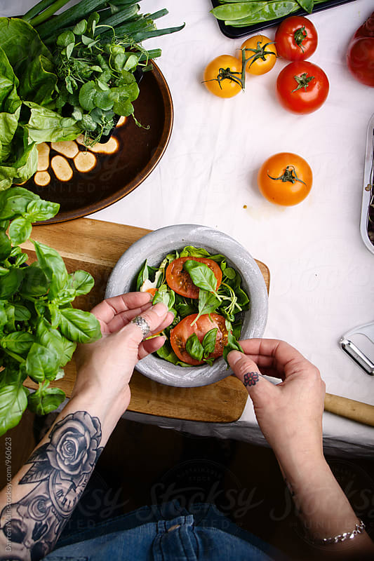 Woman preparing a salad at home. by Darren Muir for Stocksy United