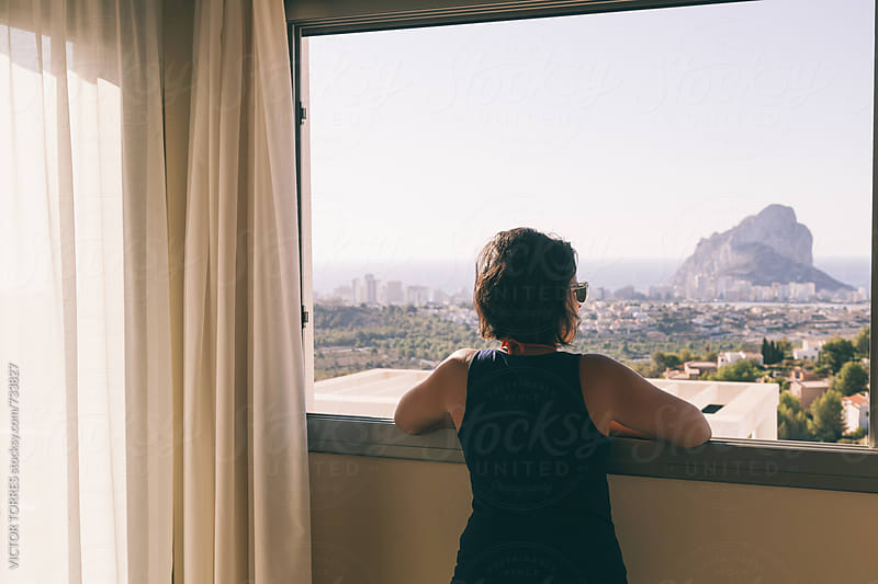 Woman Looking the Views From an Hotel Window by VICTOR TORRES for Stocksy United