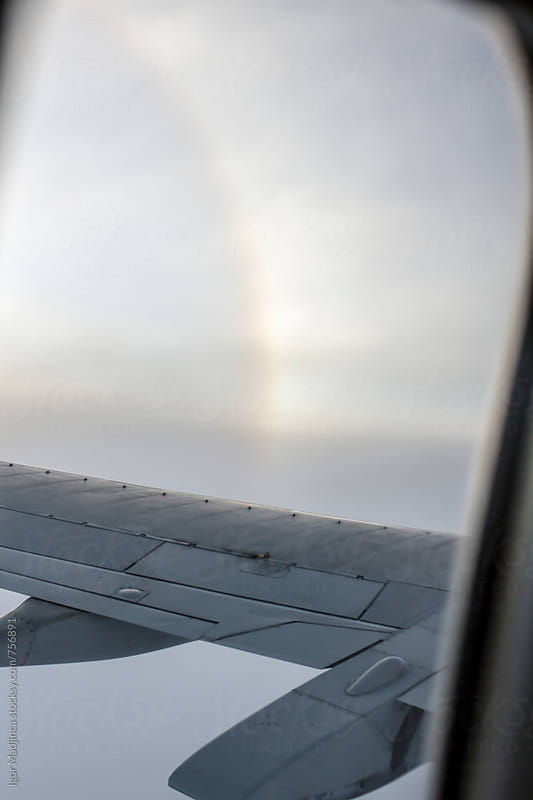 rainbow, look through the plane window by Igor Madjinca for Stocksy United