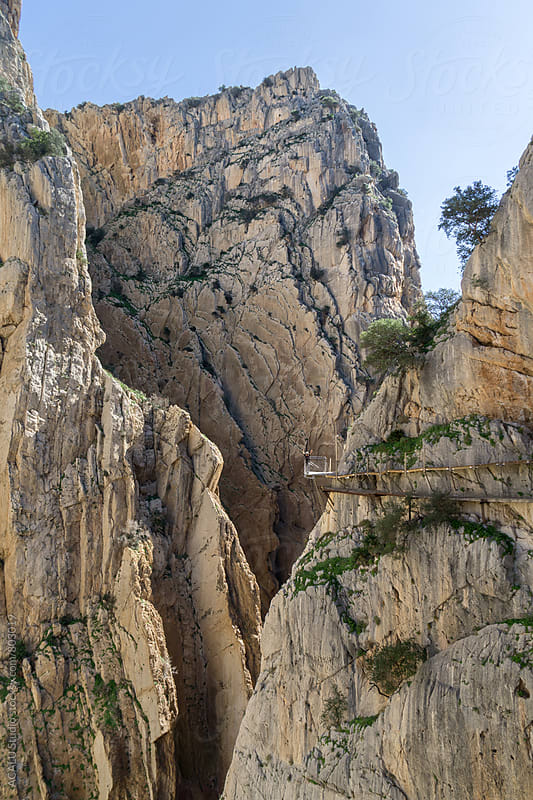 Woman saluting on the edge of a cliff in Caminito del Rey by ACALU Studio for Stocksy United