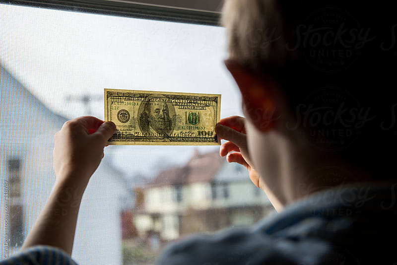 Child holds a US hundred dollar bill up to a window to see the security features by Cara Dolan for Stocksy United