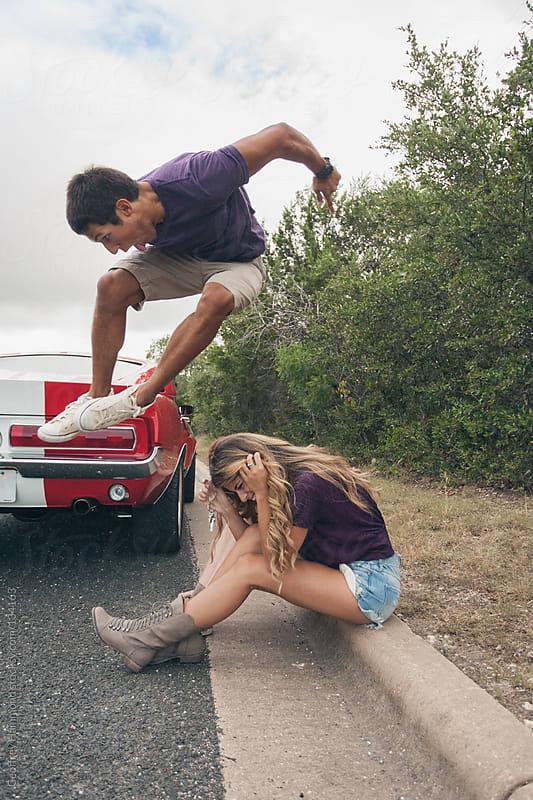 Boy jumping over girl on curb by Geoffrey Hammond for Stocksy United