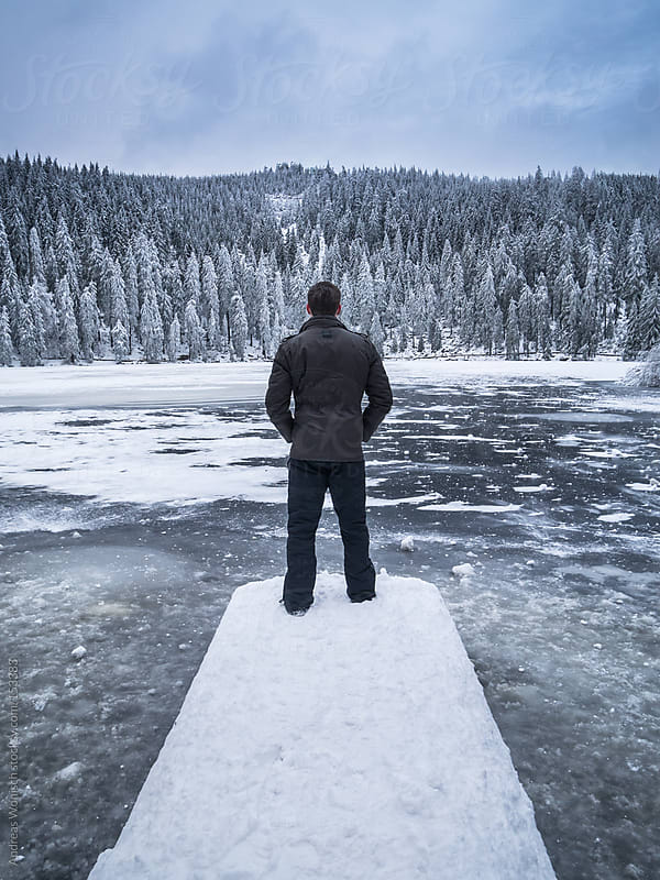 Man standing on jetty before frozen winter lake by Andreas Wonisch for Stocksy United