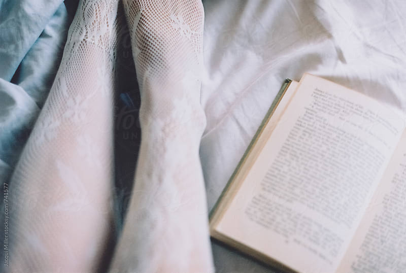 Woman's legs, in stockings, on bed with open book  by Jacqui Miller for Stocksy United