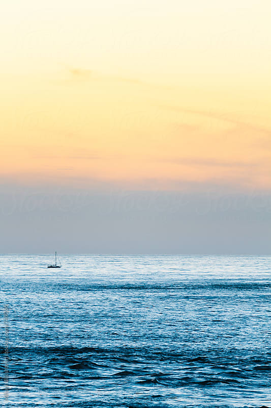Vertical view of a lone sailboat in the calm, open ocean at sunset by Mihael Blikshteyn for Stocksy United