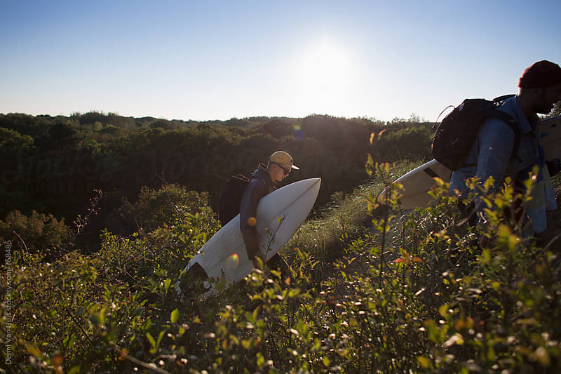 Friends hiking through the dunes with surfboards. by Denni Van Huis for Stocksy United