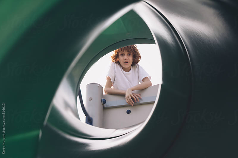 Young boy peeking down tube slide at park by Kerry Murphy for Stocksy United