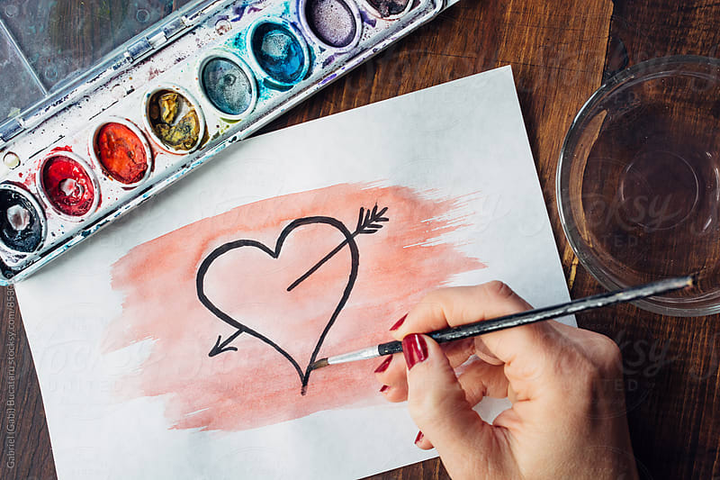 Woman's hand painting a heart in watercolor by Gabriel (Gabi) Bucataru for Stocksy United
