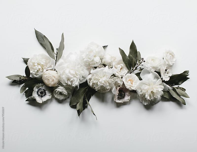 White flowers arranged on white background by Nicole Mason for Stocksy United