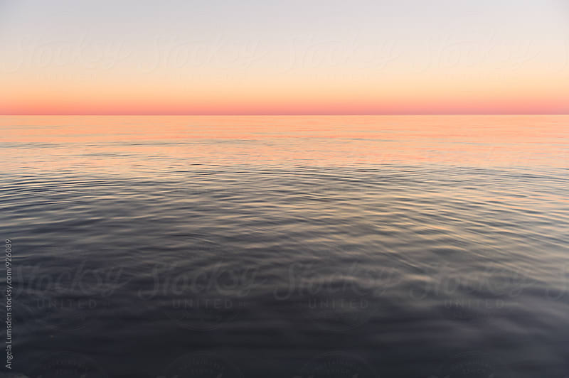 Calm waters and a cloudless sky take on an extraordinary pink glow after sunset by Angela Lumsden for Stocksy United
