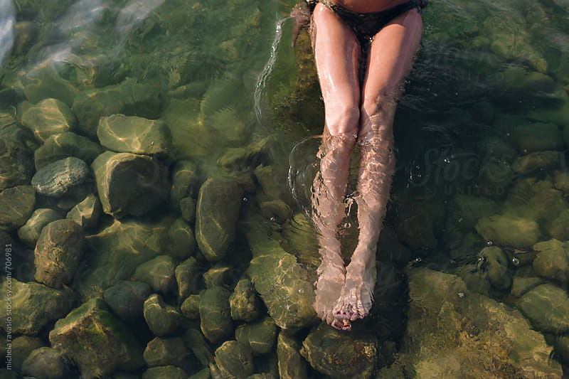 Female legs in the water by michela ravasio for Stocksy United
