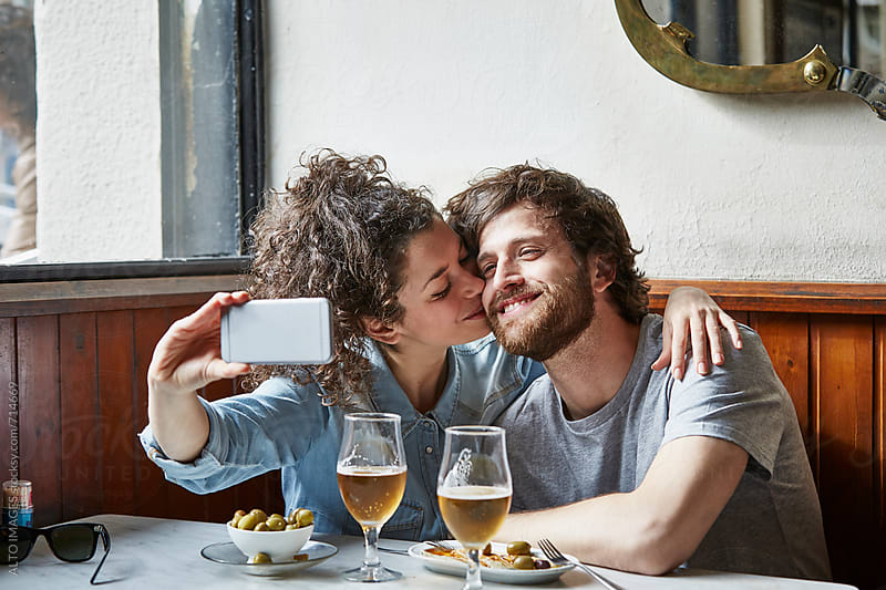 Woman Kissing Man While Taking Selfie In Restaurant by ALTO IMAGES for Stocksy United