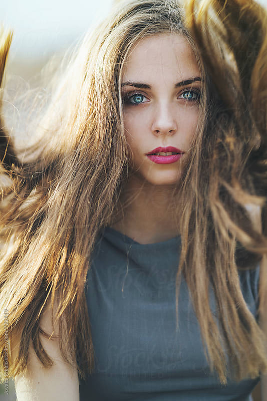 Beautiful young woman with blue eyes with wind in hair by Jovana Rikalo for Stocksy United