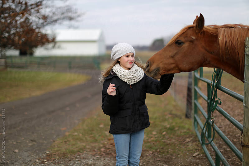 A Girl Pets A Brown Horse On A Winter Afternoon by ALICIA BOCK for Stocksy United