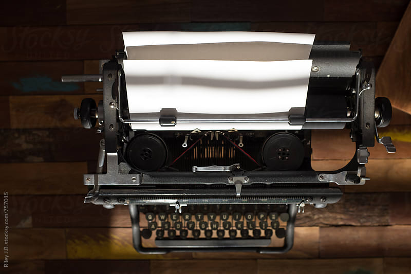 A vintage typewriter on a wooden table from above by Riley J.B. for Stocksy United