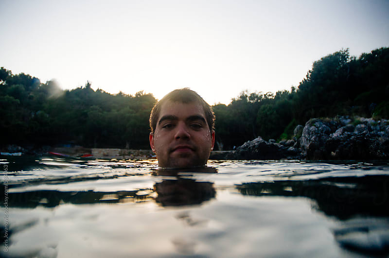 Portrait of a young man floating in the water by Boris Jovanovic for Stocksy United