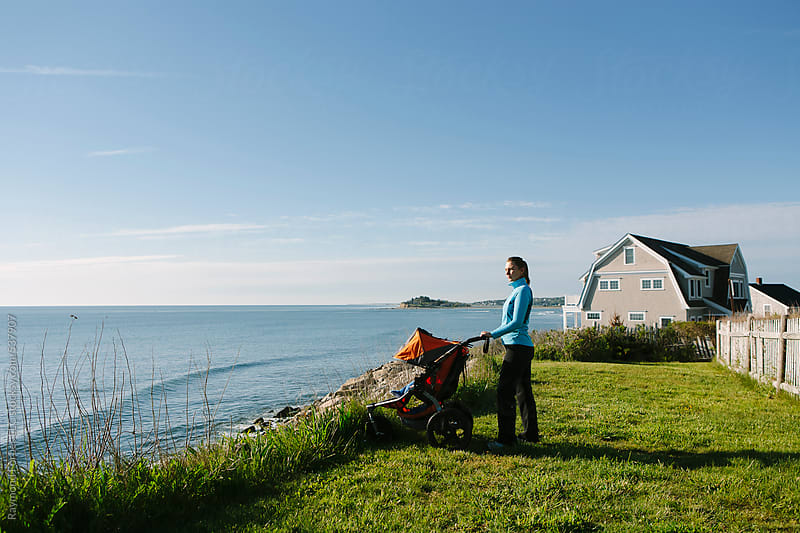 Woman at Seashore with Baby Stroller by Raymond Forbes LLC for Stocksy United