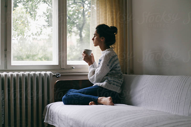 Young beautiful woman holding a cup of coffee on a couch near a window by VeaVea for Stocksy United