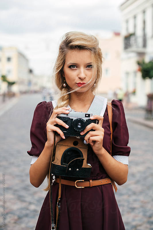 Vintage style blonde girl with retro camera by Viktor Solomin for Stocksy United