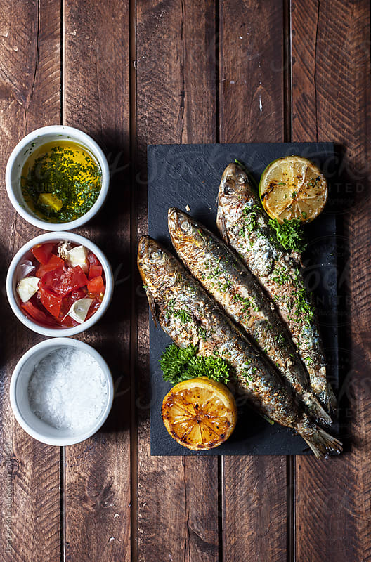 Grilled sardines and condiments.  by Darren Muir for Stocksy United