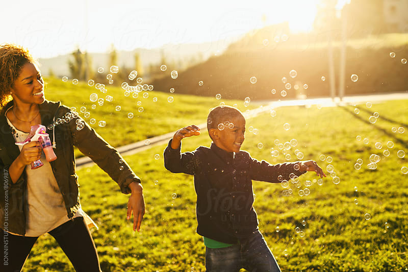 Mother and her son playing with soap bubbles in the park. by BONNINSTUDIO for Stocksy United