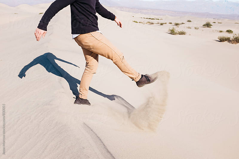 male kicking sand in swinging motion in desert sand dunes by Jesse Morrow for Stocksy United