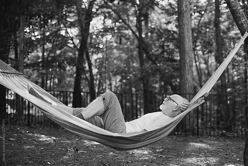 An older man relaxing in a hammock by Jakob for Stocksy United