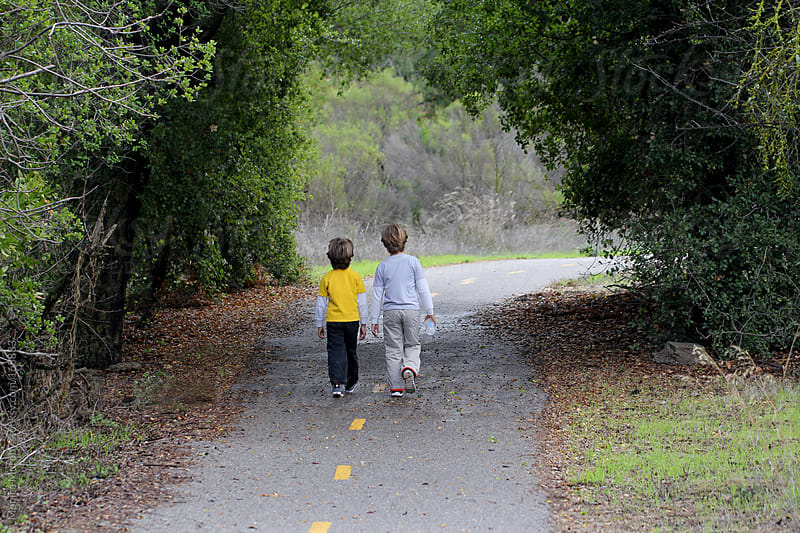 Two young boys walk down trail, through tunnel of trees by Monica Murphy for Stocksy United