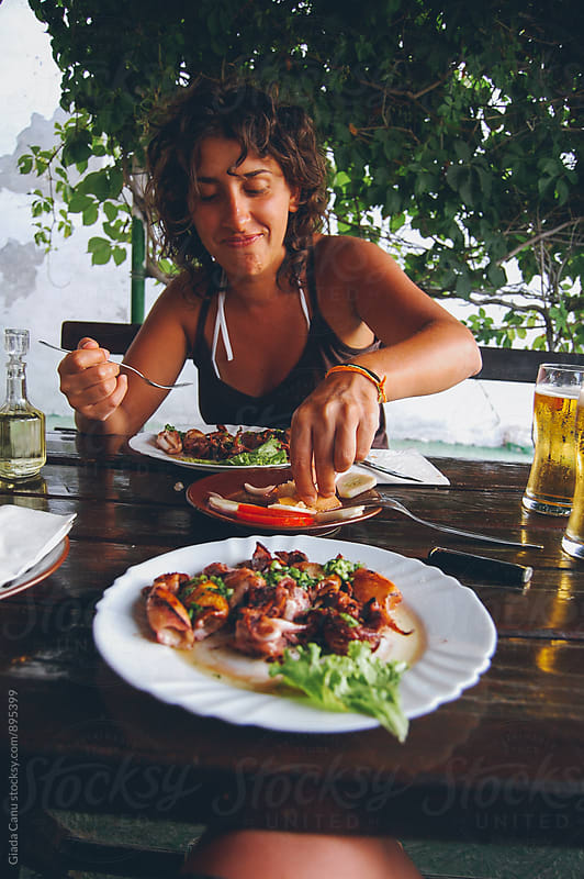Young suntanned woman eating seafood by Giada Canu for Stocksy United