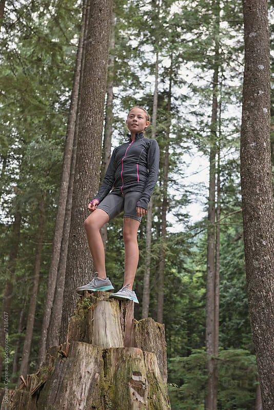 Preteen Girl Standing On Stump In Forest by Ronnie Comeau for Stocksy United