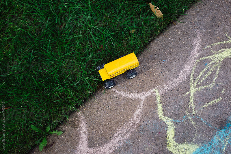 Looking down at grass, sidewalk, and a child's school bus toy. by Lucas Saugen for Stocksy United