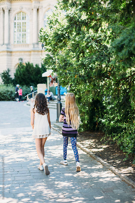 Two preteen girls walking on a pedestrian street in a urban area by Beatrix Boros for Stocksy United