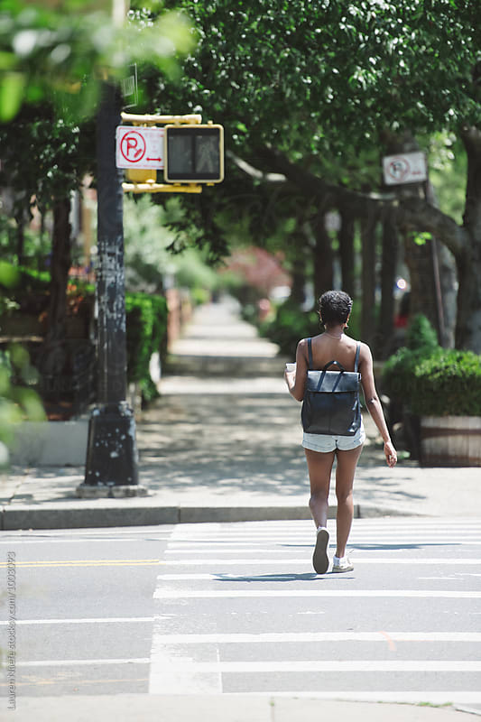 Young woman walking in her neighborhood by Lauren Naefe for Stocksy United