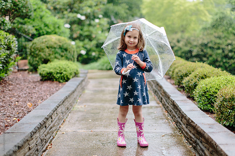 Cute young girl standing in the rain with an umbrella