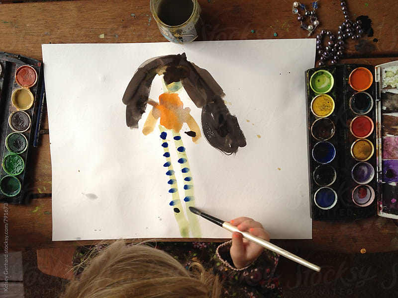 A shot from above of a young girl painting with watercolors. by Kelsey Gerhard for Stocksy United