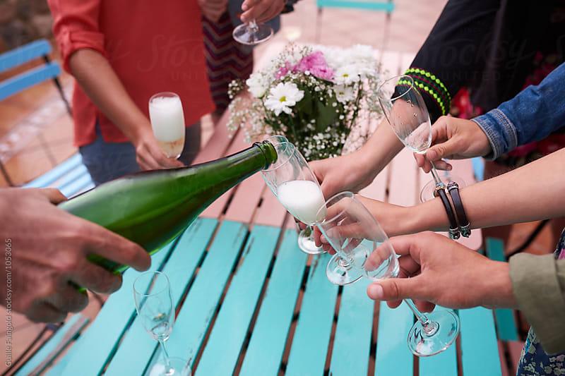 Unrecognizable friends pouring champagne in glasses