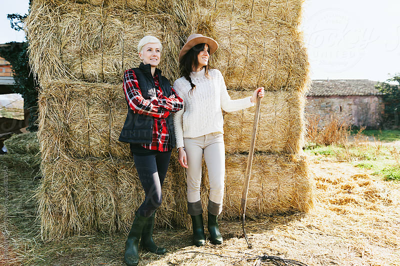 Portrait of women farmers standing in front of a haystack. by BONNINSTUDIO for Stocksy United