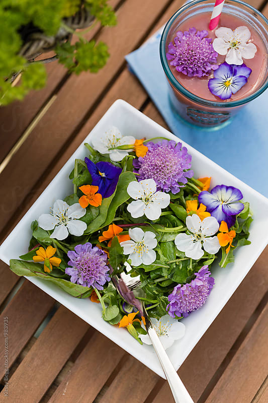 Salad bowl with edible flower garnish and a healthy fruit smoothie by Kirsty Begg for Stocksy United