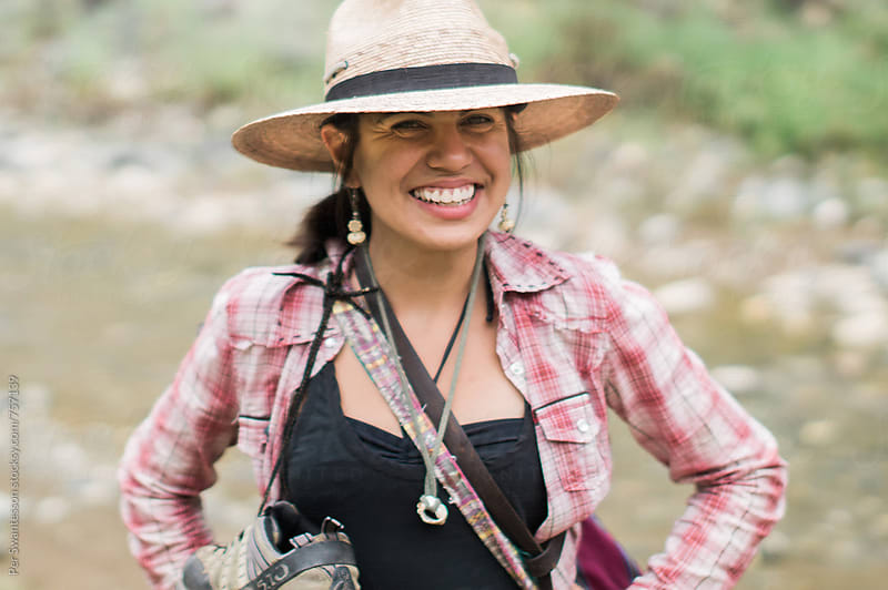 Happy young hispanic woman hiking by Per Swantesson for Stocksy United
