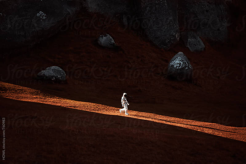 A lone astronaut descends the side of a mountain. by HOWL for Stocksy United