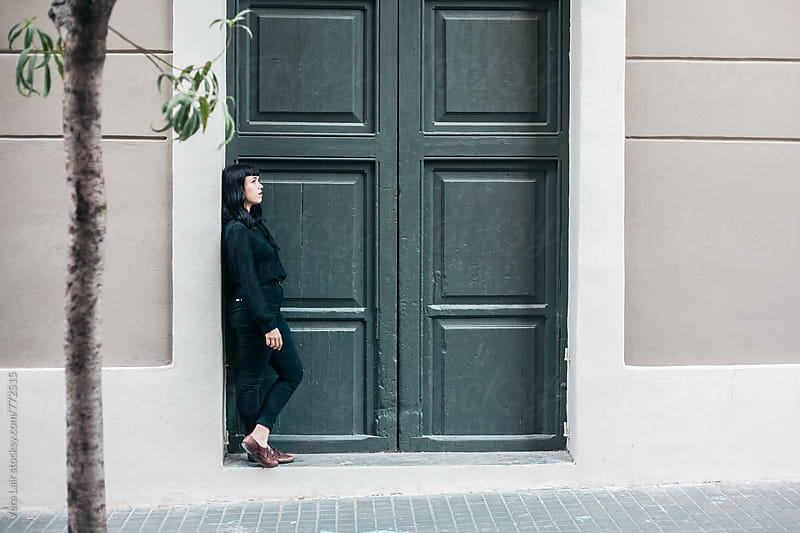 Woman waiting in front of a door by Vera Lair for Stocksy United