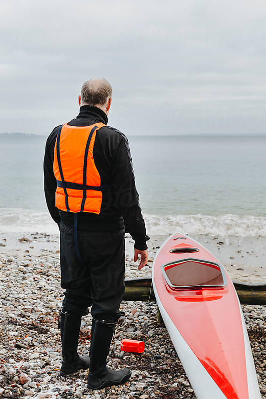 Senior man in life vest looking out at sea by Lior + Lone for Stocksy United