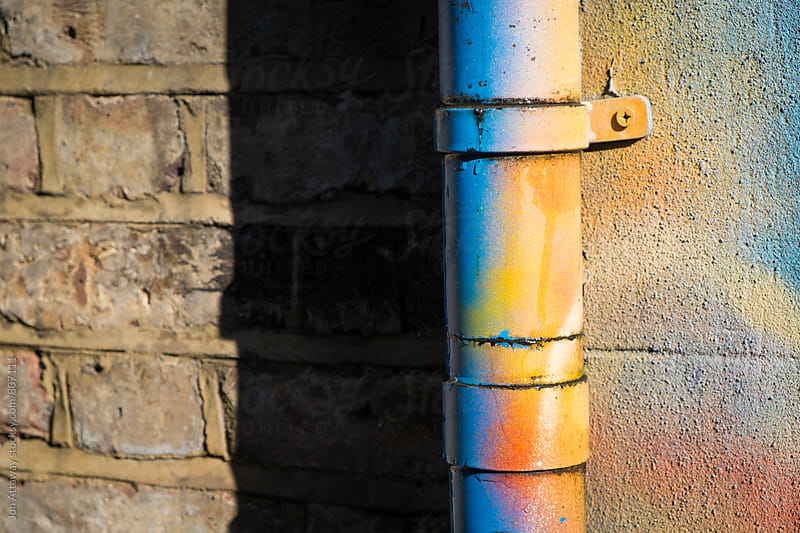 Drainpipe covered in bright spraypaint by Jon Attaway for Stocksy United