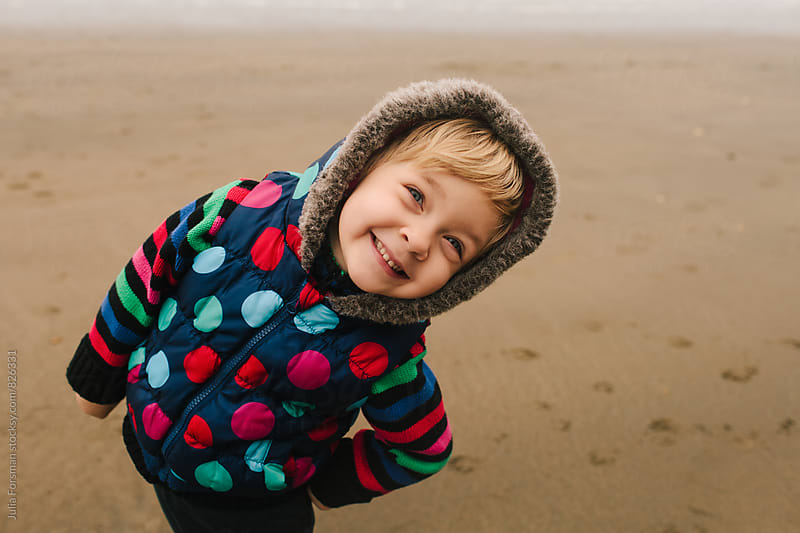 Happy, cheeky smiling girl in colourful winter clothes on a beach. by Julia Forsman for Stocksy United