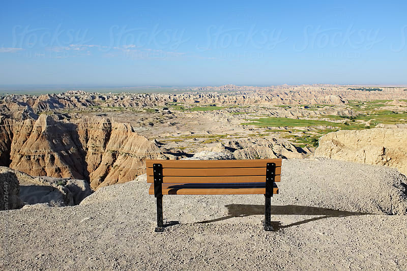 Park bench with a grand view of desolation in the Badlands of South Dakota by David Smart for Stocksy United
