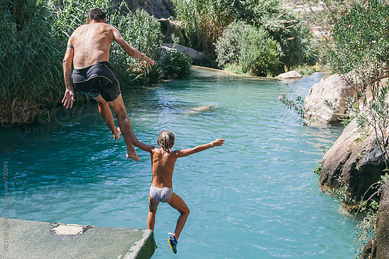 Father and Daughter Jumping into the River by VICTOR TORRES for Stocksy United