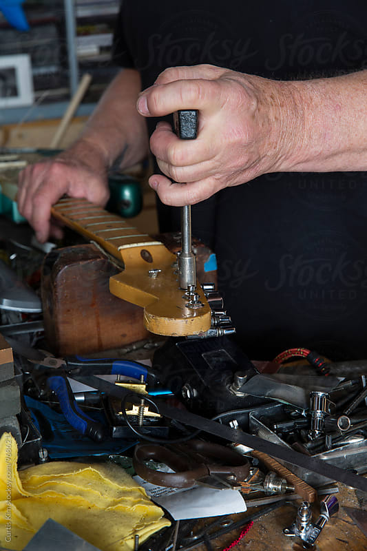 Guitar tuning machines being worked on in shop by Curtis Kim for Stocksy United