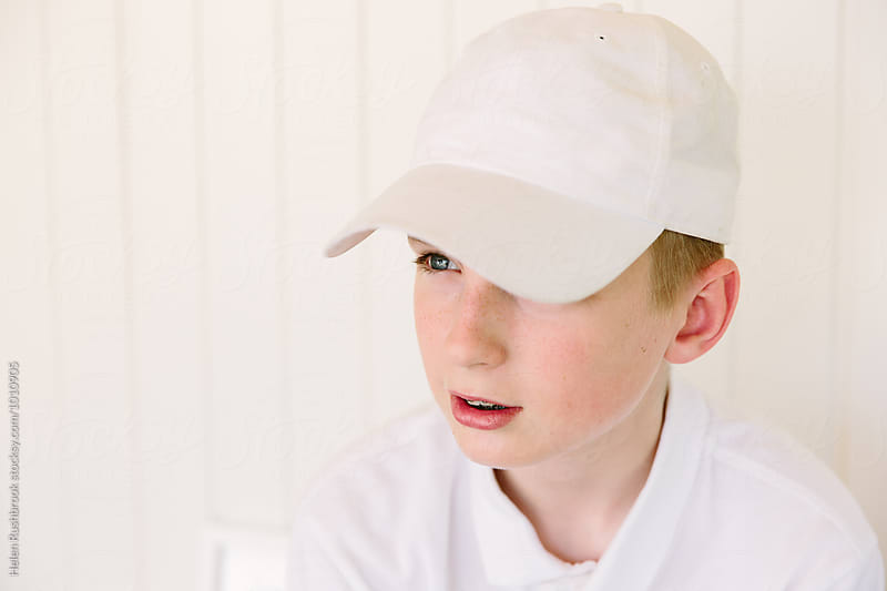 Teenage boy wearing a white baseball cap and polo shirt. by Helen Rushbrook for Stocksy United